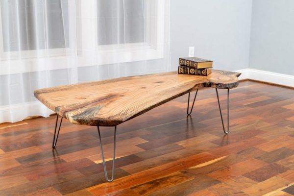red oak live edge coffee table with two books in living area