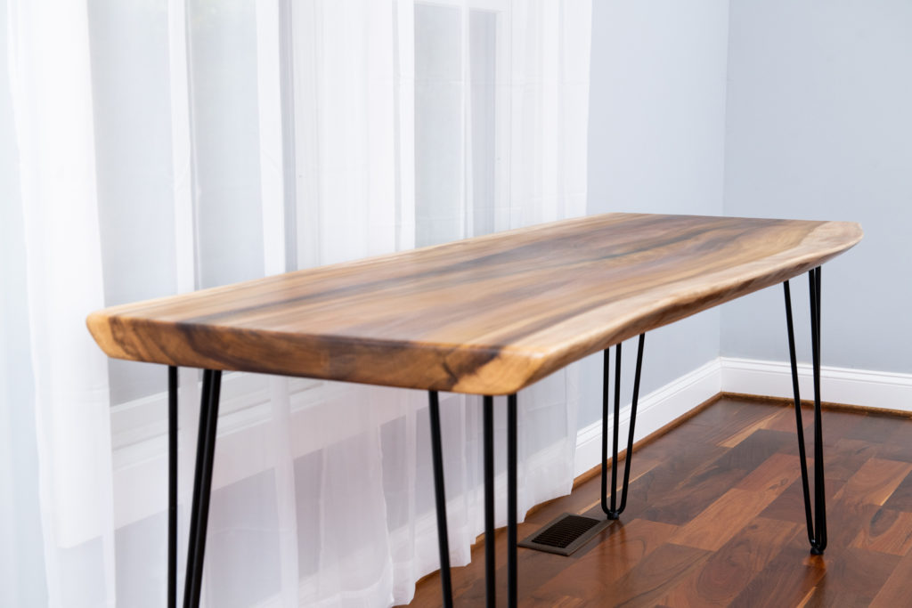 tall finished wood slab table on display