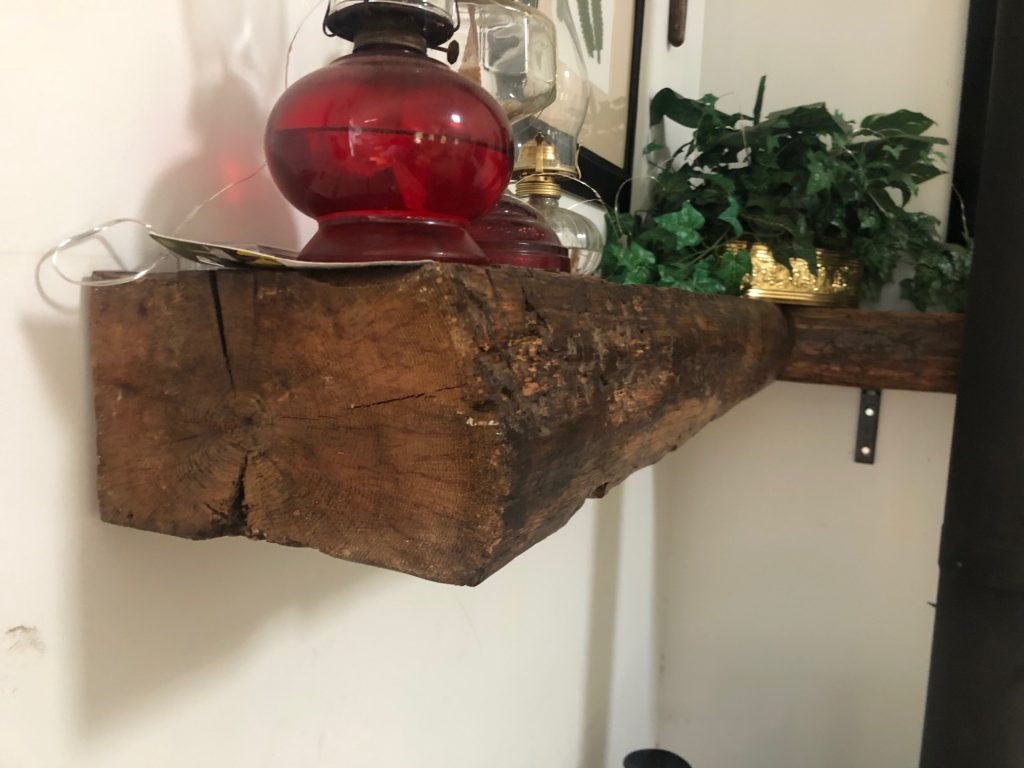 unsmoothed wood shelf holding decorations in a house